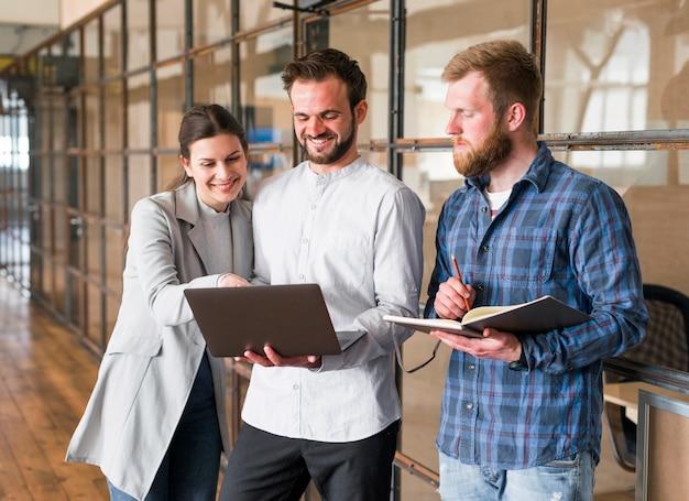 Happy businesspeople lavorando insieme sul progetto in ufficio