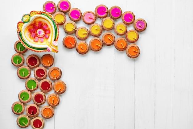 Happy diwali - le lampade di clay diya si sono accese durante il dipavali, festival indù della celebrazione delle luci. diya tradizionale variopinto della lampada a olio su fondo di legno bianco