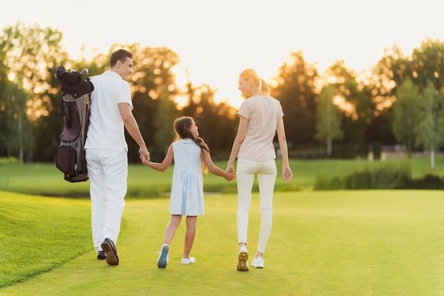 Happy family lascia il campo da golf dopo partita.