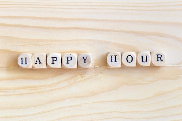 Happy hour, parola di viste superiori fatta dalle lettere di legno sulla tavola