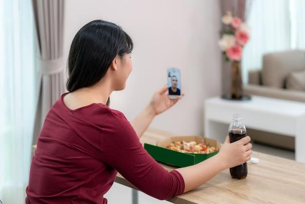 Happy hour virtuale della donna asiatica che incontra la cena e che mangia l'alimento della pizza online insieme al suo ragazzo nella videoconferenza con la compressa digitale