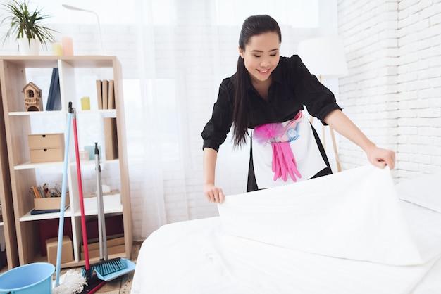 Happy maid con nuovo set di biancheria da letto pulito in camera