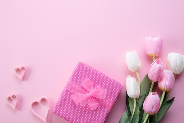 Happy mothers day con vista dall'alto di fiori rosa tulipano, scatola regalo e cuore di carta