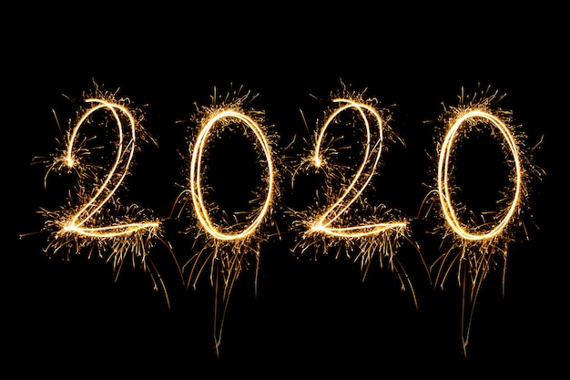 Happy new year 2020. testo creativo happy new year 2020 scritto scintillanti stelle filanti isolati