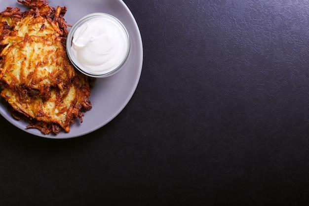 Hash marrone e panna acida su un piatto su uno sfondo di pietra scura