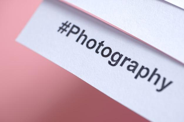 Hashtag popolare 'fotografia' stampato su carta bianca su rosa