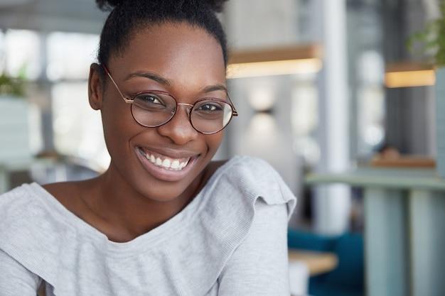 Headshot di femmina africana dalla pelle scura attraente positiva in occhiali rotondi, esprime piacevoli emozioni