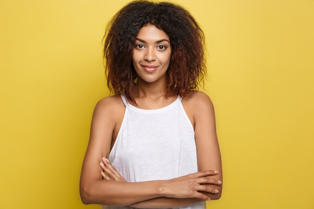 Headshot ritratto di bella attraente donna afroamericana postando armi attraversate con sorridente felice. sfondo di studio giallo. copia spazio.