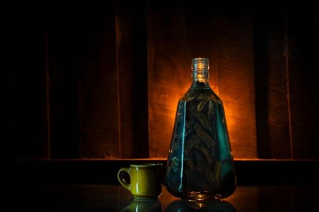 Herb mescola whisky nel barattolo. nel bar / sul vecchio tavolo di legno che ha il bicchiere di whisky a