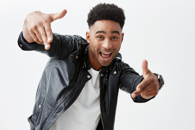 Hey amico. emozioni positive. giovane bell'uomo dalla pelle nera con acconciatura afro in abiti casual che punta con la mano a porte chiuse con espressione faccia eccitata, in posa per la foto sulla festa.
