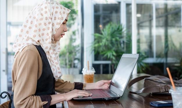 Hijab da portare delle giovani free lance femminili che per mezzo di un computer portatile
