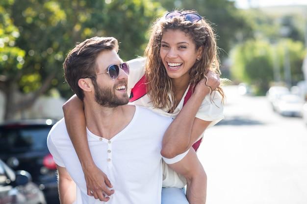 Hip uomo dando piggy back alla sua fidanzata per la strada