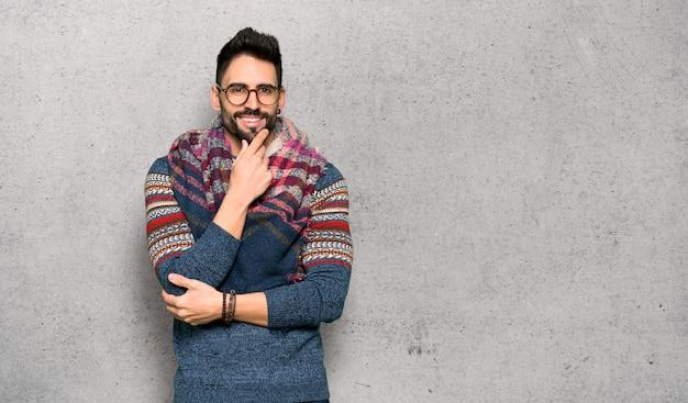 Hippie uomo con gli occhiali e sorridente sulla parete strutturata