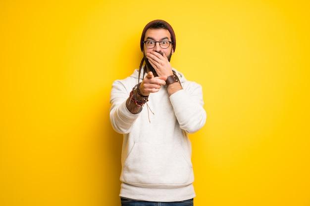 Hippie uomo con i dreadlocks che puntava il dito contro qualcuno e rideva