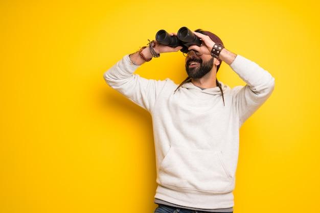 Hippie uomo con i dreadlocks e guardando in lontananza con il binocolo
