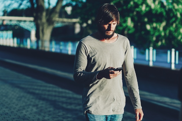 Hipster cammina per la città con un telefono.