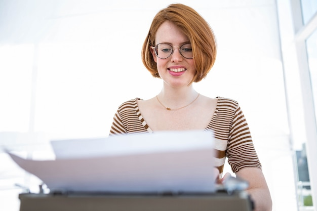 Hipster digitando su una macchina da scrivere che è su una scrivania in legno