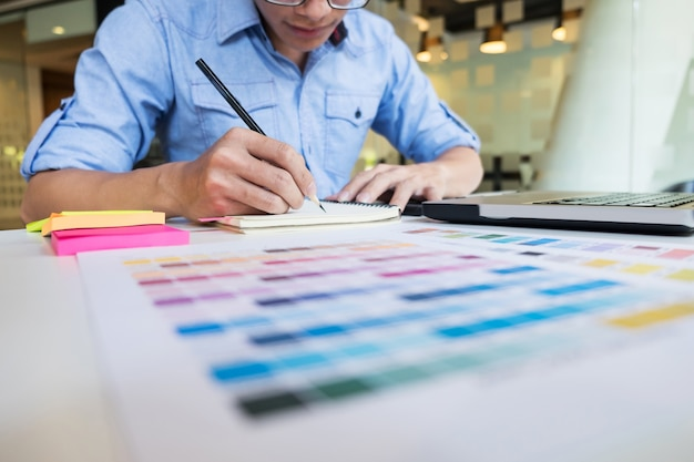 Hipster moderno disegnatore grafico lavorando a casa utilizzando il computer portatile in ufficio.