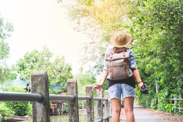 Hipster ragazza asiatica con la respirazione della fotocamera e guardando tropicale passerella e canale, viaggiatore turistico in asia posizione