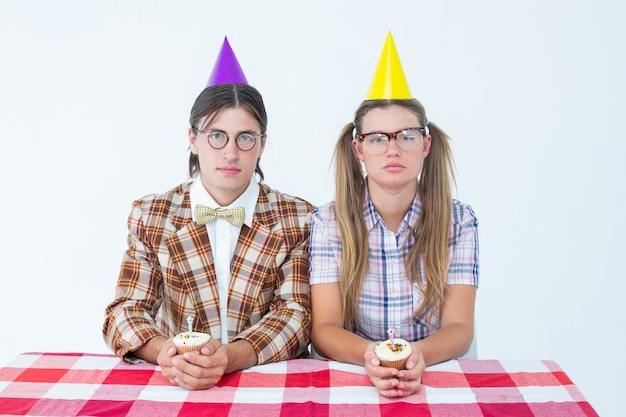 Hipsters geeky unsmiling che celebra il compleanno