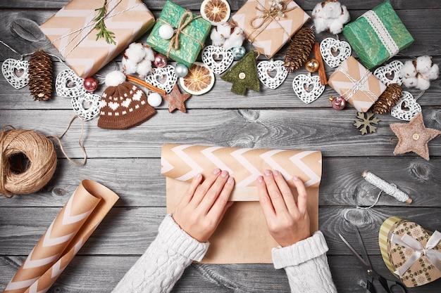 Hobby creativo regali di natale con strumenti e decorazioni. imballaggio presenta sul tavolo di legno, vista dall'alto.