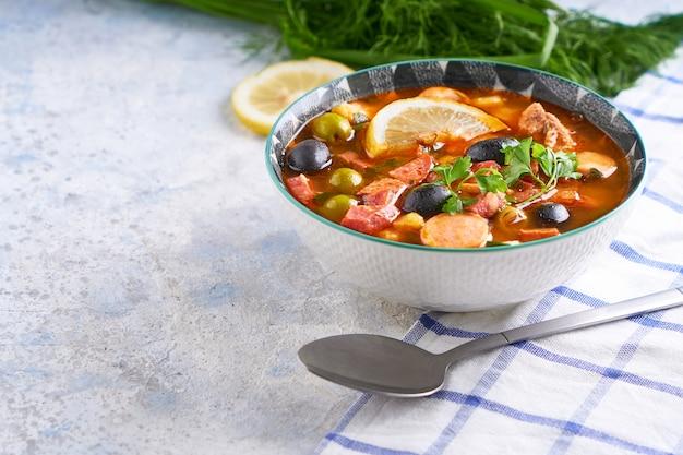Hodgepodge tradizionale della minestra in piatto sulla tavola bianca copyspace
