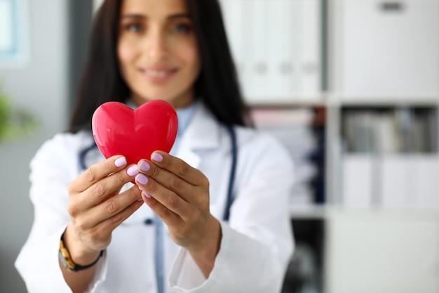 Holding femminile del cardiologo nel cuore rosso del giocattolo di armi