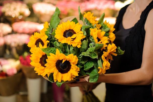 Holding femminile del fiorista del negozio di fiori dei girasoli del mazzo