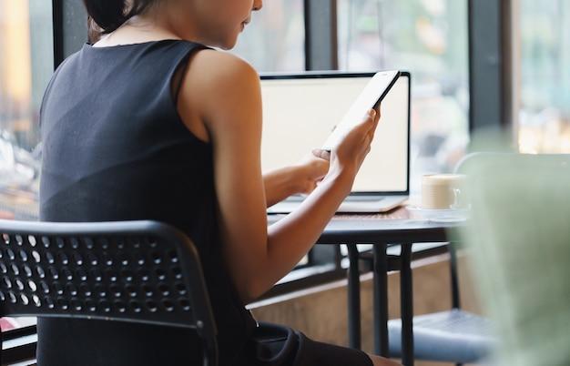 Holding femminile e guarda al telefono nella caffetteria
