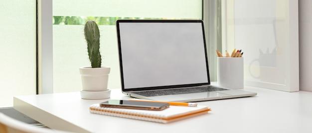 Home office moderno con mock up laptop, cancelleria e decorazioni sul tavolo bianco vicino alla finestra
