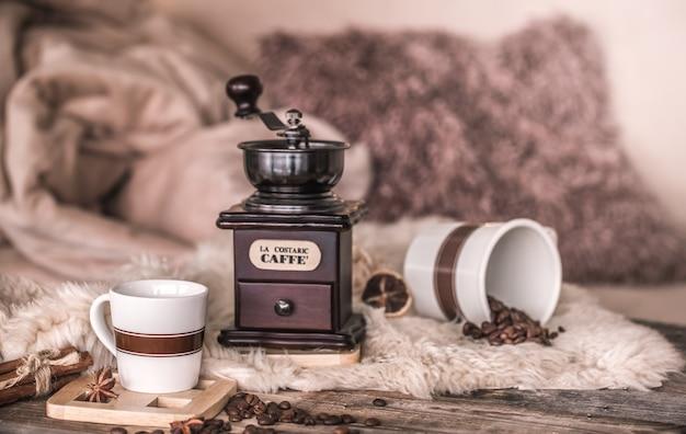 Home still life negli interni con un vecchio macinacaffè e una tazza di chicchi di caffè, sul muro di un accogliente arredamento per la casa