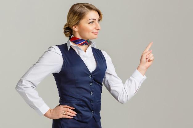 Hostess affascinante vestita in uniforme blu che punta il dito su grigio