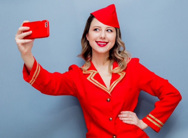 Hostess che indossa in uniforme rossa con il cellulare
