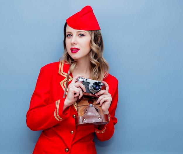 Hostess che indossa in uniforme rossa con macchina fotografica d'epoca