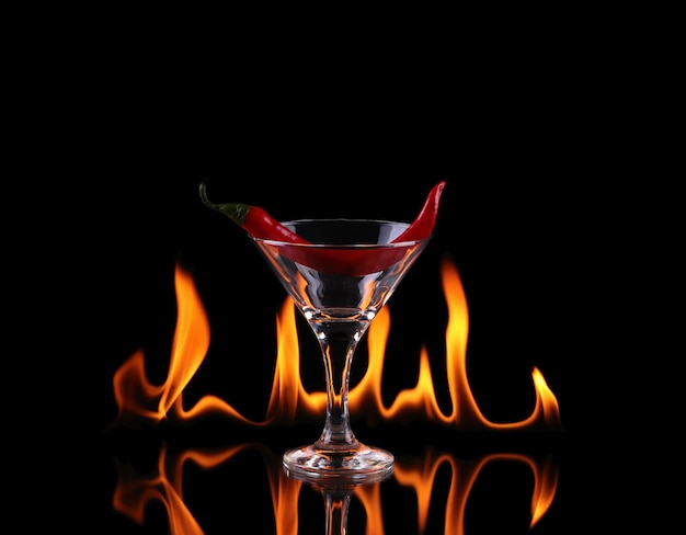 Hot chili pepper in un bicchiere da martini con un fuoco su uno sfondo nero