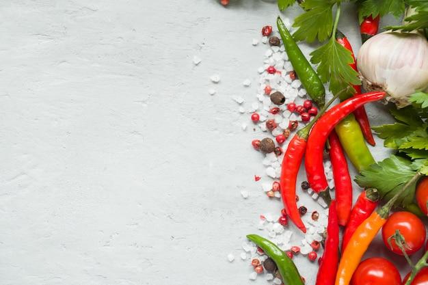 Hot chili peppers multicolore, pomodoro ciliegia su ramo, aglio e altre spezie