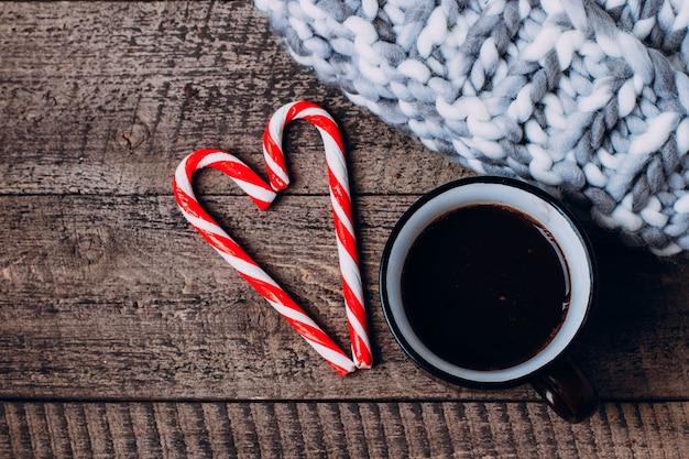 Hot chocolate e candy stick su berretto a maglia. tradizionale bevanda natalizia invernale.