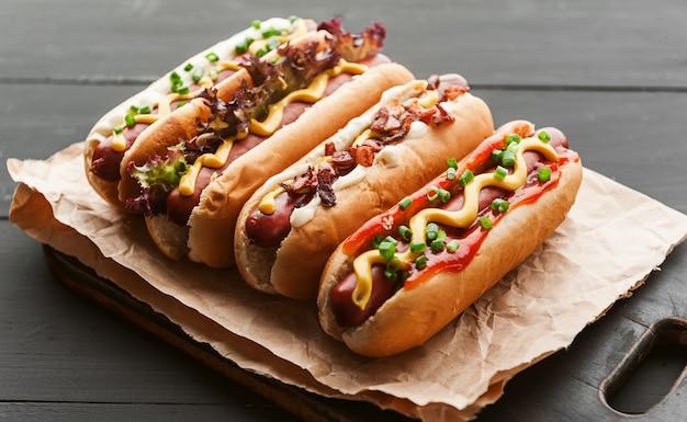 Hot dog alla griglia con senape americana gialla, su uno sfondo di legno scuro