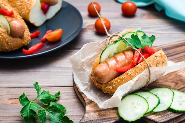 Hot dog appetitoso pronto da salsiccia fritta, panini e verdure fresche, avvolto in carta pergamena su un tagliere su un tavolo di legno
