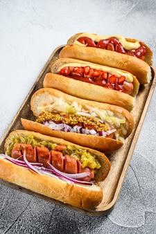 Hot dog completamente caricati con condimenti assortiti su un vassoio. deliziosi hot dog con salsicce di maiale e manzo. sfondo bianco. vista dall'alto