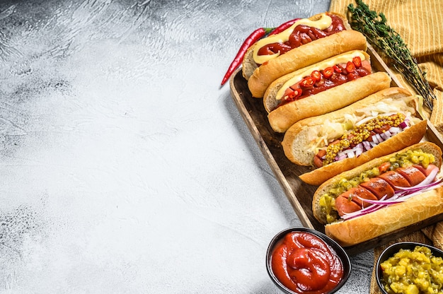 Hot dog con condimenti assortiti. deliziosi hot dog con salsicce di maiale e manzo. sfondo bianco