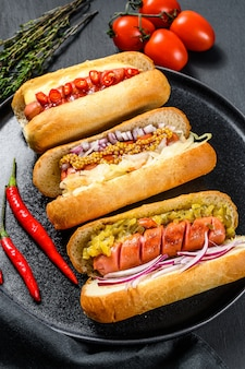 Hot dog con condimenti assortiti. deliziosi hot dog con salsicce di maiale e manzo. sfondo nero. vista dall'alto