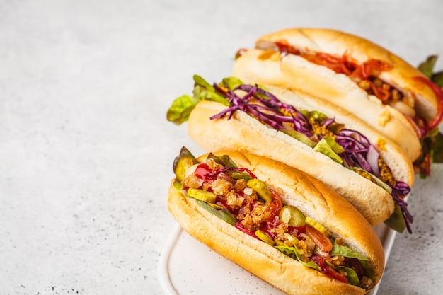 Hot dog con condimenti assortiti su uno sfondo bianco, vista dall'alto.