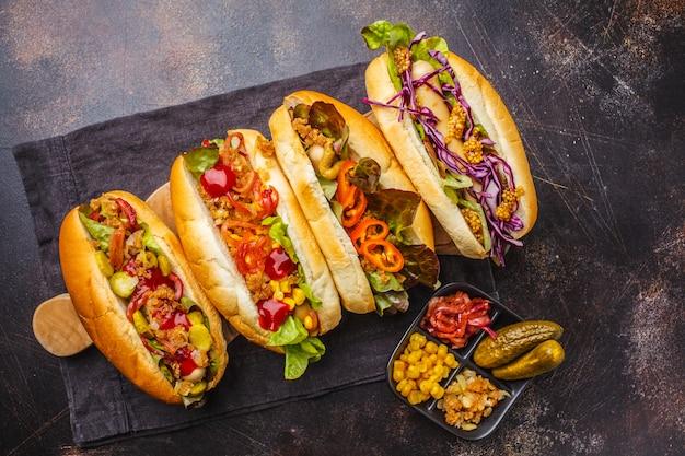 Hot dog con condimenti assortiti su uno sfondo scuro, vista dall'alto.