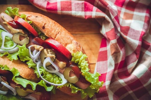 Hot dog con insalata e pomodori freschi sul bordo di legno