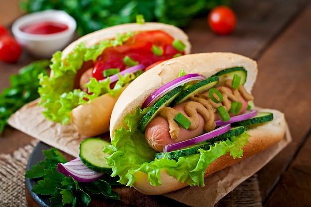 Hot dog con ketchup, senape, lattuga e verdure sulla tavola di legno