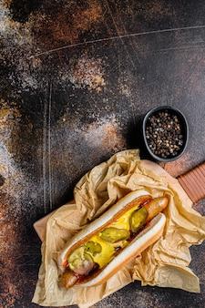 Hot dog con la salsiccia di pollo su un tagliere di legno in carta kraft, concetto del menu del fast food. cibo spazzatura. spazio per il testo