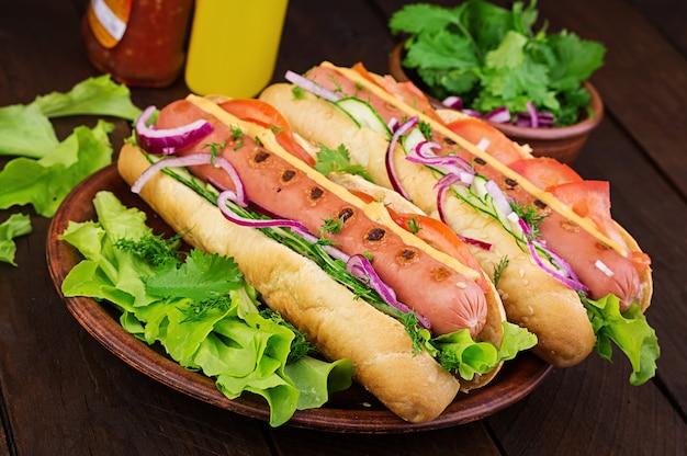 Hot dog con salsiccia, cetriolo, pomodoro e lattuga sul tavolo di legno scuro. hot dog estivo.