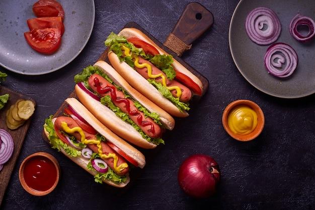 Hot dog con salsiccia, cipolla fritta, foglie di coriandolo, salsa di formaggio e senape. fast food. vista dall'alto, copia spazio