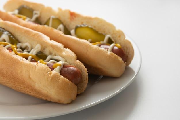 Hot dog fatti in casa con salsicce e cetrioli sottaceto nel piatto
